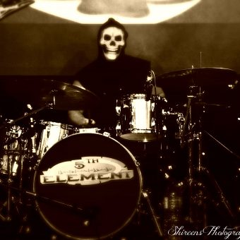 Aaron playing drums, wearing a grim reaper mask. Black and white.
