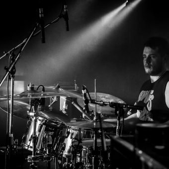 Aaron playing drums, black and white.