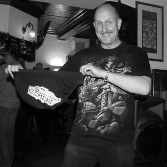 Richard smiling and holding up a special pair of 5th Element underpants he's been given as a leaving gift. Black and white.