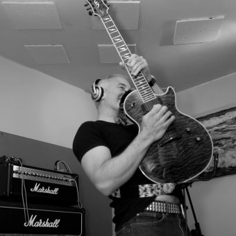 Neil posing while playing his guitar in the studio.