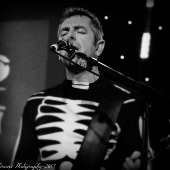 Alan singing on his mic, black and white.