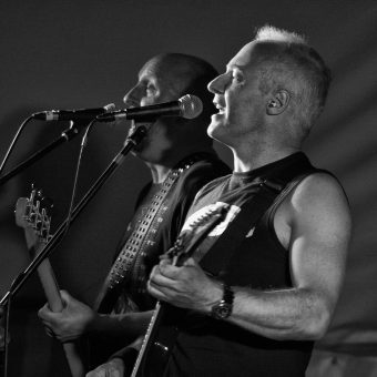 Richard and Neil singing on their mics, black and white.