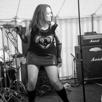 Ann head-banging on stage. Black and white.