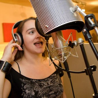 Ann singing on the microphone in the studio.