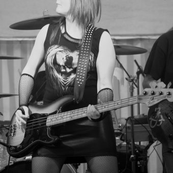 Ann playing Richard's bass and pulling a funny face. Black and white.