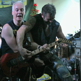 Neil and Alan reaching over each other to play each other's guitars.