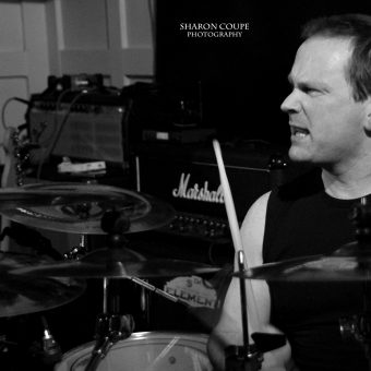 Phil singing and playing drums, black and white.