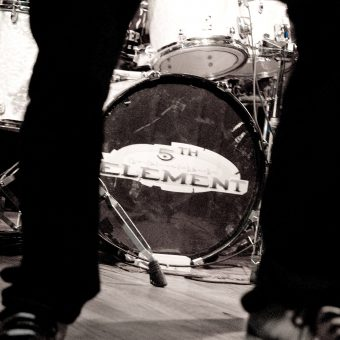 The 5th Element logo on the bass drum, in black and white.