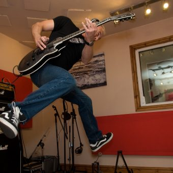 Neil jumping while playing guitar in the studio.