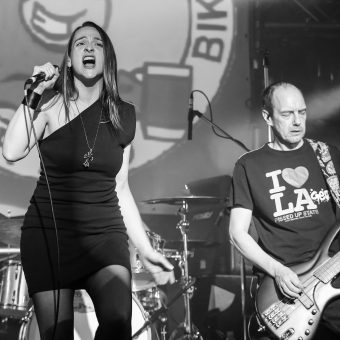 Ann holding her mic and singing while Dave plays bass, with the No Bull rally logo in the background. Black and white.