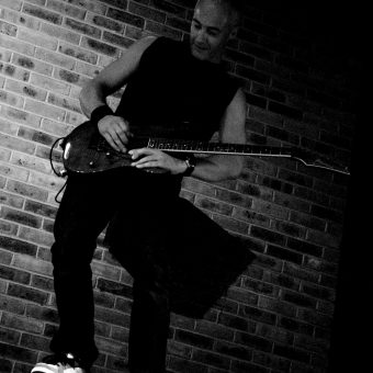 Neil posing with his guitar on top of a speaker, in black and white.