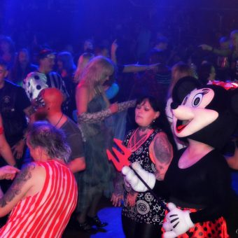 The crowd dancing, all dressed up for Halloween. One person is wearing a large Minnie Mouse head.
