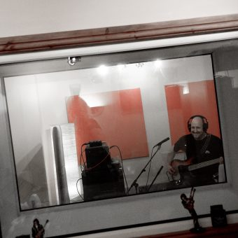 Richard playing bass through the window in the studio.