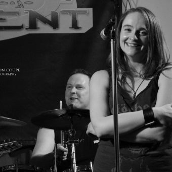 Ann smiling with her arms folded, Phil grinning behind her on the drum kit.