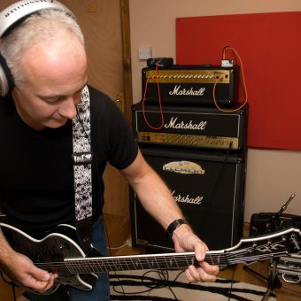 Neil playing guitar in the studio.