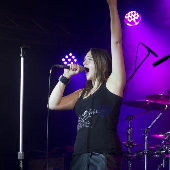 Ann singing, left arm raised.