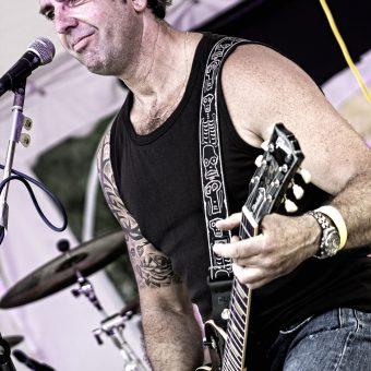 Alan playing guitar and smiling.