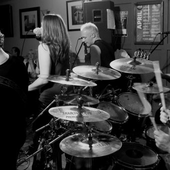 The band performing, from behind the stage, black and white.