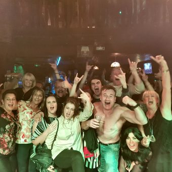 The crowd at Bootleggers Bar, Kendal, cheering and waving their arms. A man in the middle has his shirt off.