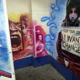 A mural graffiti design of the Hulk's screaming face, the beggar girl design on the adjacent wall.