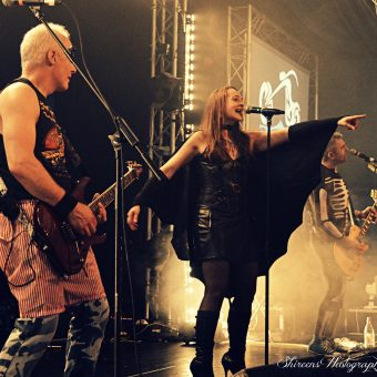 Ann, wearing bat wings, singing and pointing to the crowd as Neil and Alan sing on their mics on either side of her.