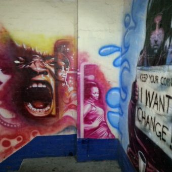 A mural graffiti design of the Hulk's screaming face, the beggar girl design on the adjacent wall.