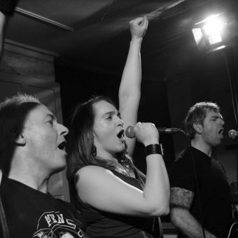 Neil, Ann and Alan all singing with their arms raised. black and white.