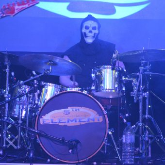 Aaron playing drums, wearing a grim reaper mask.