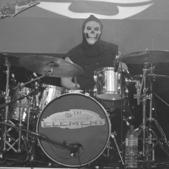 Drummer Aaron wearing a grim reaper mask and hood as he sits behind his drum kit, Black and white.