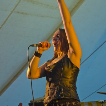 Ann singing, left hand raised.