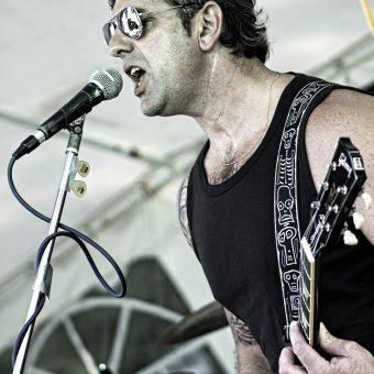 Alan singing on his mic, wearing shades.