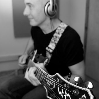 Close up of Neil playing his guitar at the studio, black and white.