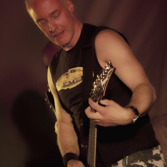 Close up of Neil playing guitar.