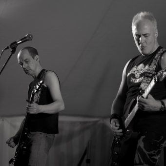 Dave and Neil performing on stage, black and white.
