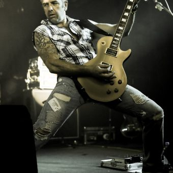 Alan posing in a wide-legged stance while playing guitar.