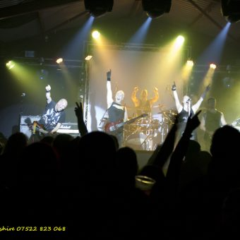 The band and the crowd singing together, arms raised.