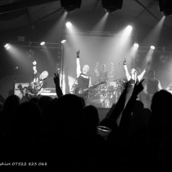 The band on stage at No Bull, arms raised, with the audience waving their arms in the foreground. Black and white.