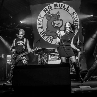 The whole band performing on stage, with the No Bull rally logo in the background. Black and white.