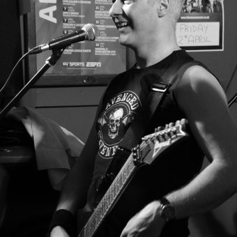Neil smiling on the mic, black and white.