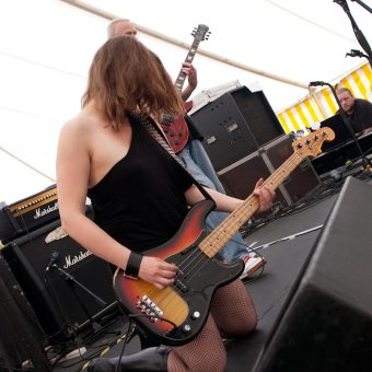 Ann playing bass on her knees.