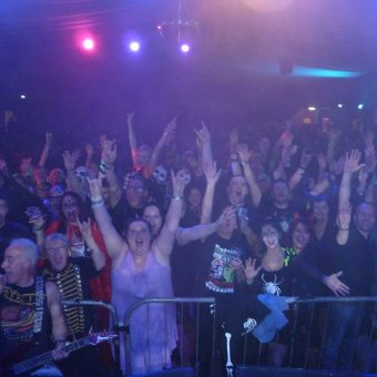 The crowd at the Original Cruisers' Halloween Rock Night, cheering and waving their arms.