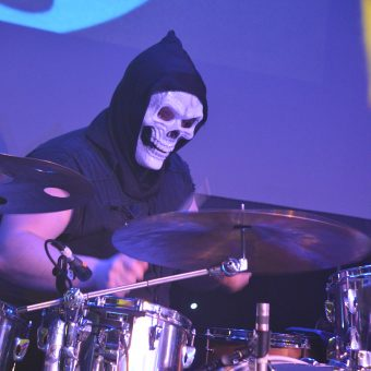 Aaron playing drums wearing a grim reaper mask.
