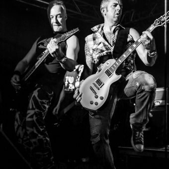 Neil and Alan performing on stage, black and white.
