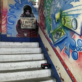 A mural graffiti design of a beggar girl holding a sign that says 'Keep your coins, I want change.'
