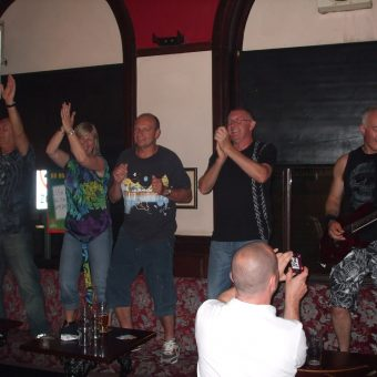 The crowd at the Old Bank Inn, Blackpool, dancing on the seats next to Neil playing guitar.