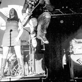 Alan jumping off the drum riser, high knees. Black and white.