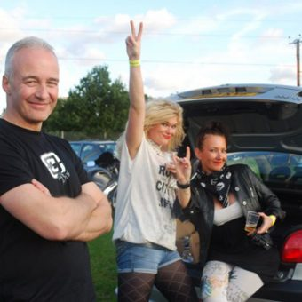 Neil on the left, standing grinning with his arms folded. In the background, an attractive blonde girl smiles and gives the peace sign next to her friend, an attractive brunette, who sits in the boot of their open car giving the rock salute.