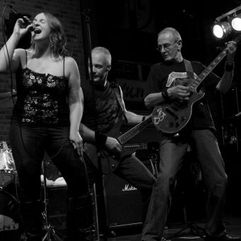 Ann, Neil and Rocker performing on stage. Black and white.