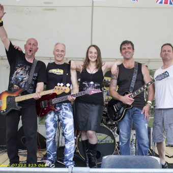 The band posing for a group photo on stage.
