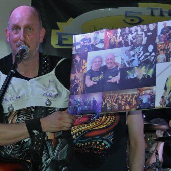 Richard holding up a canvas presented to him by the band.